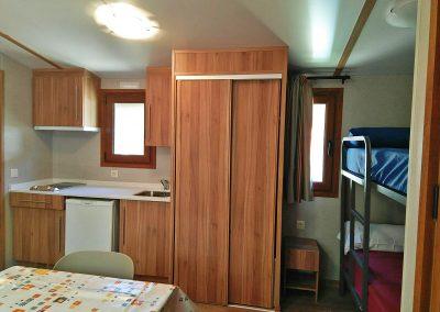 Sala de estar, cocina y cabina con literas